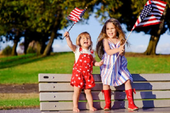 Picture of two happy kids waving the American flag on a bench.